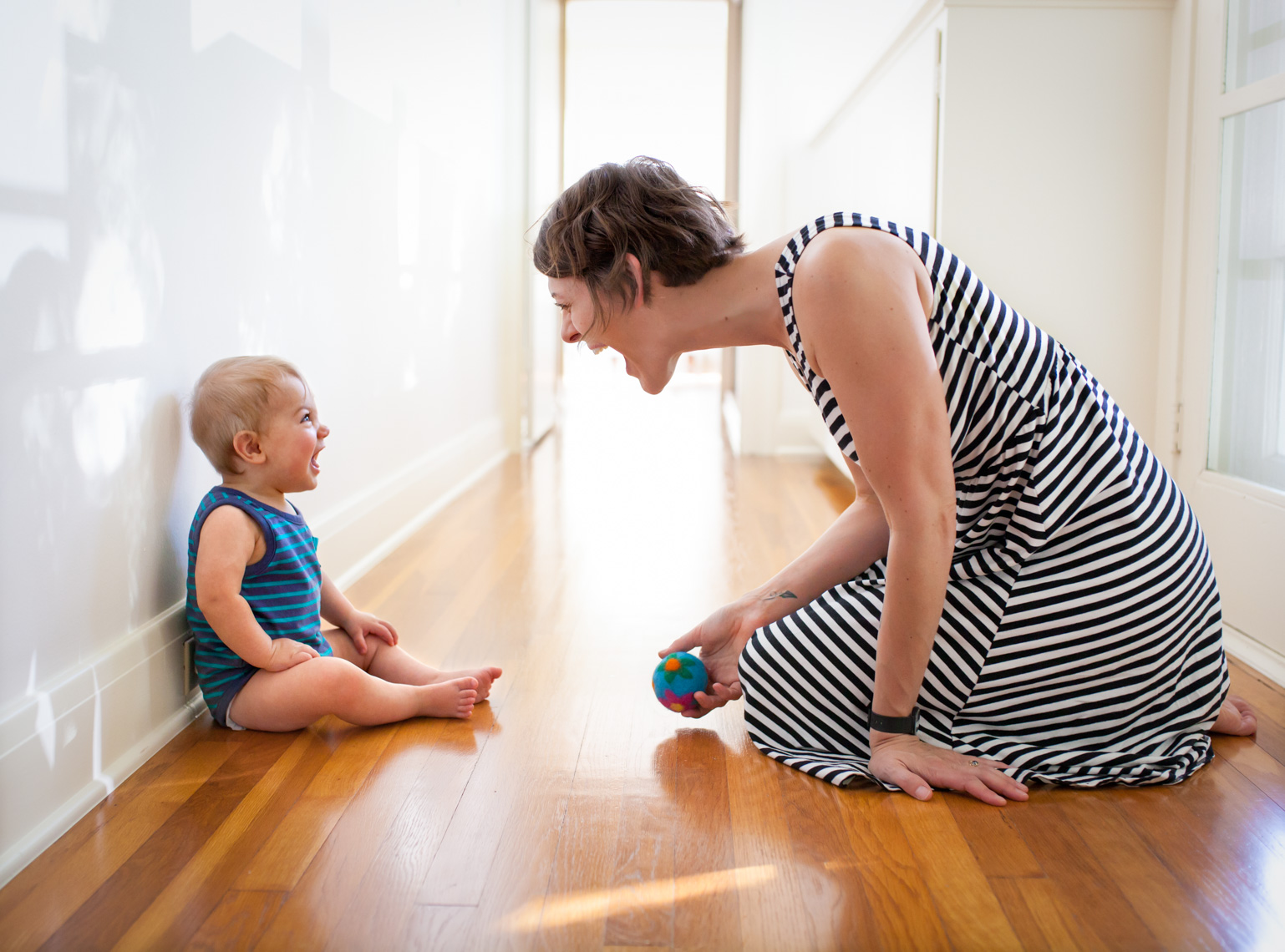 Lifestyle image of mom and baby playing on floor | Tosca Radigonda Photography
