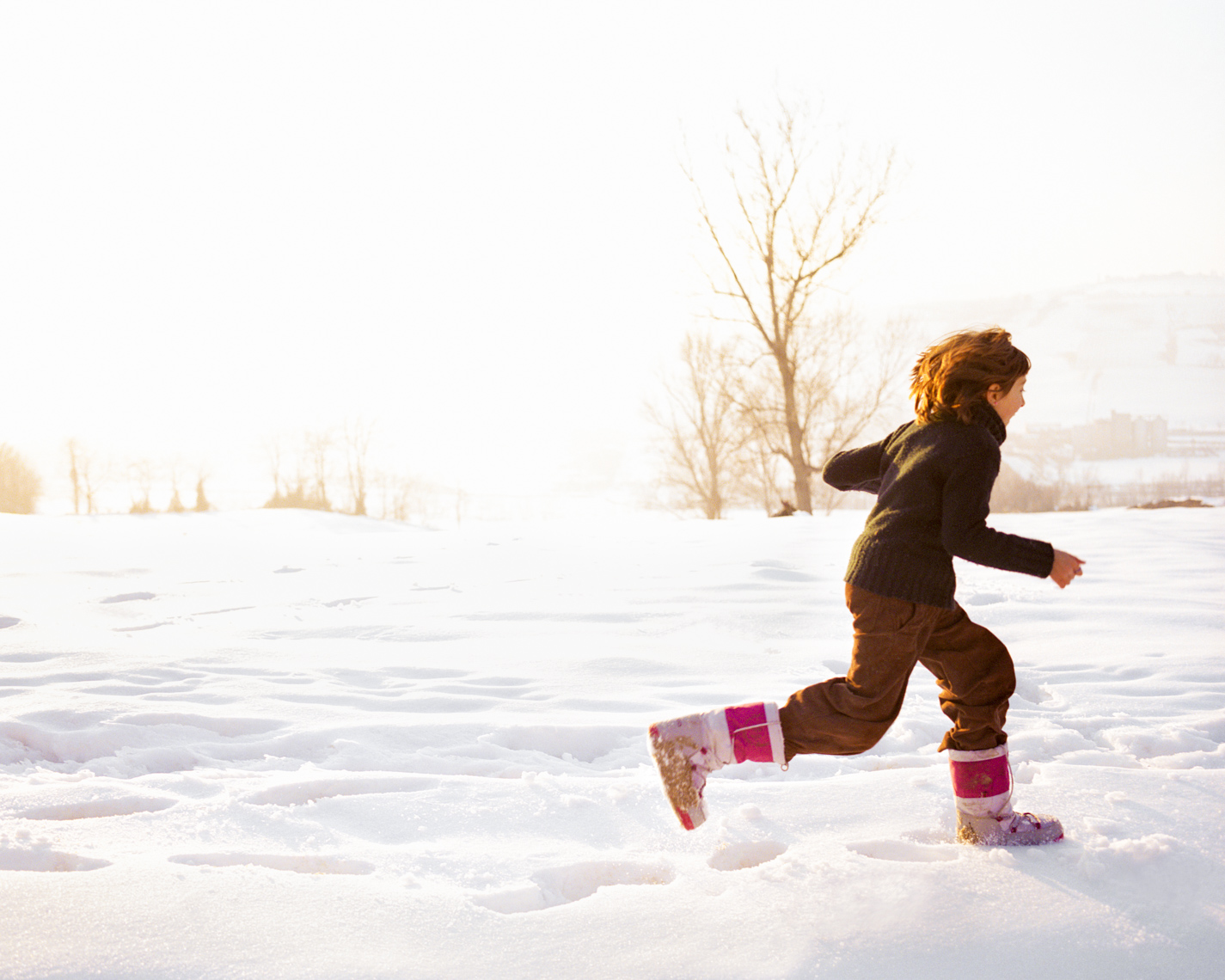 Uplifting image of girl running in snow | Commercial Lifestyle Photographer